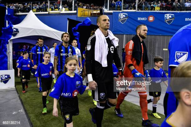 Evan Bush of the Montreal Impact and Stefan Frei of the Seattle Sounders are being escorted to the field by children during the MLS game at Olympic...