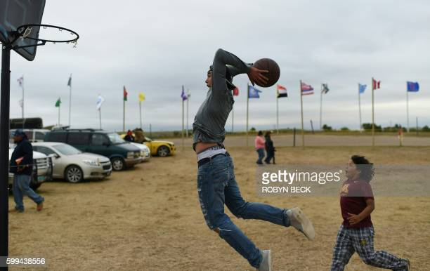 Evan Butcher of the Chippewa Tribe plays basketball with younger boys September 4, 2016 at the encampment near Cannon Ball, North Dakota where...