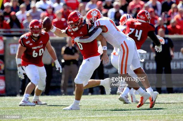 Evan Conley of the Louisville Cardinals runs with the ball while sacked by Isaiah Simmons of the Clemson Tigers at Cardinal Stadium on October 19...
