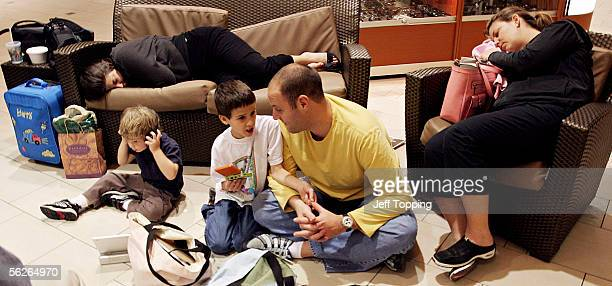 Evan Dechtman of Denver Colorado talks with his nephew Ryan Beckett while his son Barry listens to music and his sisterinlaw Marnie Miller and his...