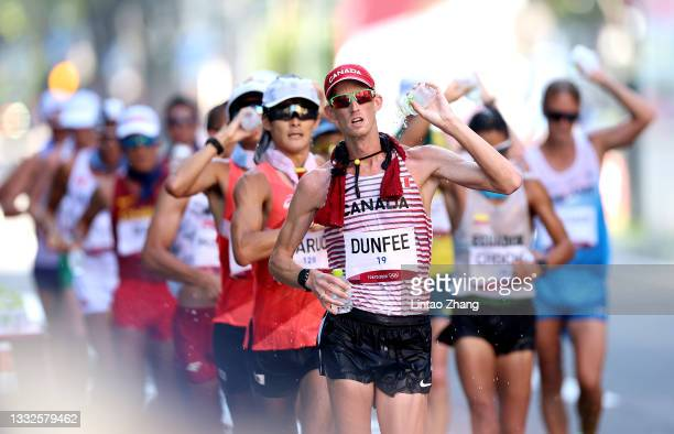 Evan Dunfee of Team Canada grabs water as he competes in the Men's 50km Race Walk Final on day fourteen of the Tokyo 2020 Olympic Games at Sapporo...