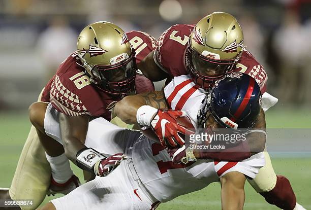 Evan Engram of the Mississippi Rebels is tackled by Ro'Derrick Hoskins and Derwin James of the Florida State Seminoles in the first half during the...
