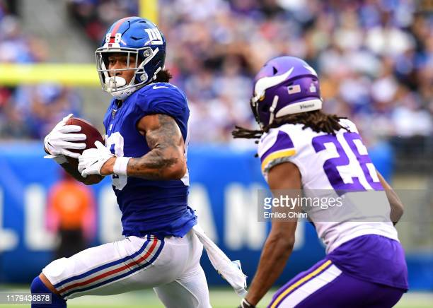 Evan Engram of the New York Giants carries the ball with pressure from Trae Waynes of the Minnesota Vikings during their game at MetLife Stadium on...