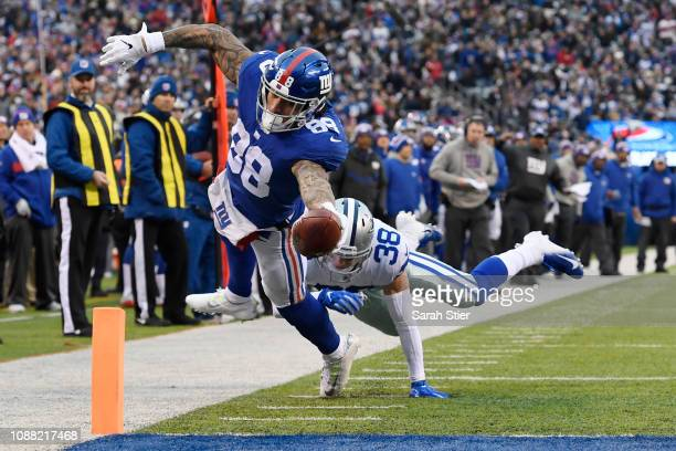 Evan Engram of the New York Giants dives into the end zone for a touchdown during the third quarter of the game against the Dallas Cowboys at MetLife...