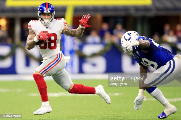 Evan Engram of the New York Giants runs the ball in the game against the Indianapolis Colts in the third quarter at Lucas Oil Stadium on December 23...