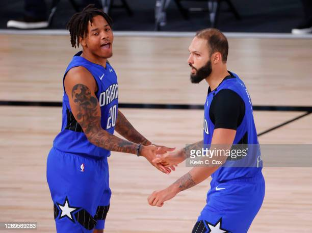 Evan Fournier celebrates with Markelle Fultz of the Orlando Magic after shooting a three point basket against the Milwaukee Bucks during the fourth...