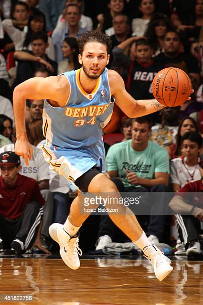 Evan Fournier of the Denver Nuggets handles the ball against the Miami Heat at the American Airlines Arena in Miami Florida on March 14 2014 NOTE TO...