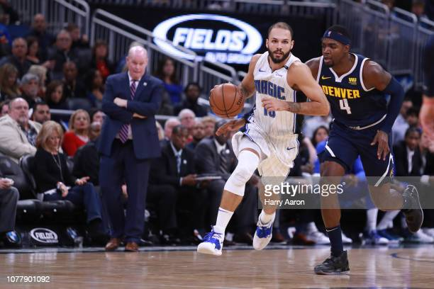 Evan Fournier of the Orlando Magic charges gown the court with Paul Millsap of the Denver Nuggets as Head Coach Steve Clifford of the Orlando Magic...