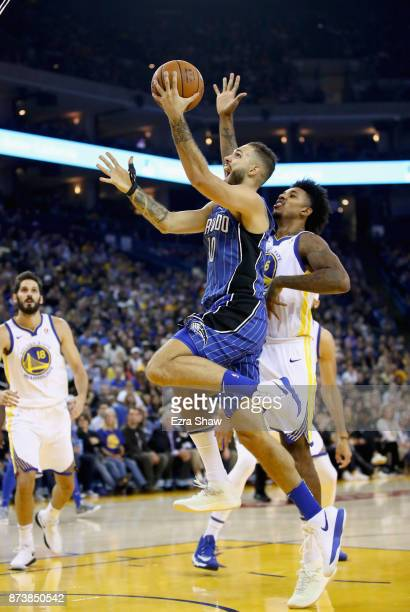 Evan Fournier of the Orlando Magic drives on Nick Young of the Golden State Warriors at ORACLE Arena on November 13 2017 in Oakland California NOTE...