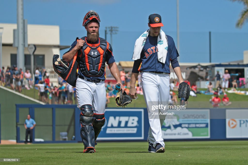 Evan Gattis #11 and Collin McHugh #31 of the Houston Astros walk to the dugout for the start of the spring training game agains the Atlanta Braves at The Ballpark of the Palm Beaches on February 24, 2018 in West Palm Beach, Florida.