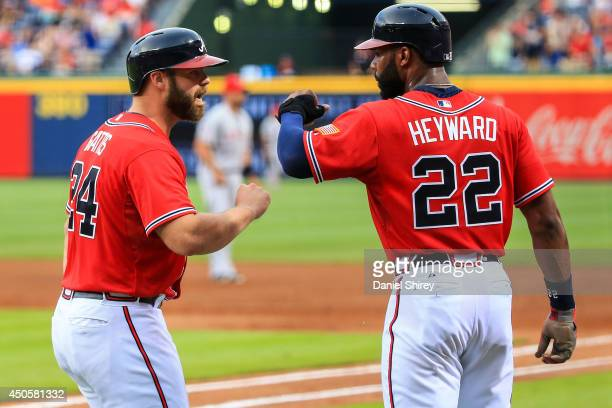 Evan Gattis celebrates a three-run home run with Jason Heyward of the Atlanta Braves in the first inning against the Los Angeles Angels of Anaheim at...