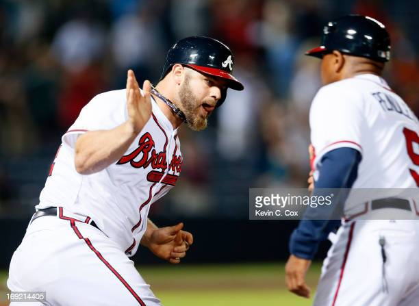 Evan Gattis of the Atlanta Braves celebrates his solo homer in the bottom of the ninth that tied the game 4-4 against the Minnesota Twins with first...