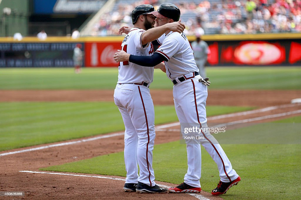Evan Gattis #24 of the Atlanta Braves celebrates with Freddie Freeman #5 after scoring against the Philadelphia Phillies during the first inning at Turner Field on June 18, 2014 in Atlanta, Georgia.