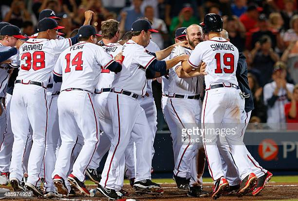 Evan Gattis of the Atlanta Braves celebrates with his teammates after hitting a walk-off homer in the tenth inning that scored Dan Uggla in their 4-2...