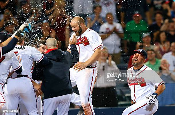 Evan Gattis of the Atlanta Braves celebrates with his teammates after hitting a walkoff homer in the tenth inning that scored Dan Uggla in their 42...