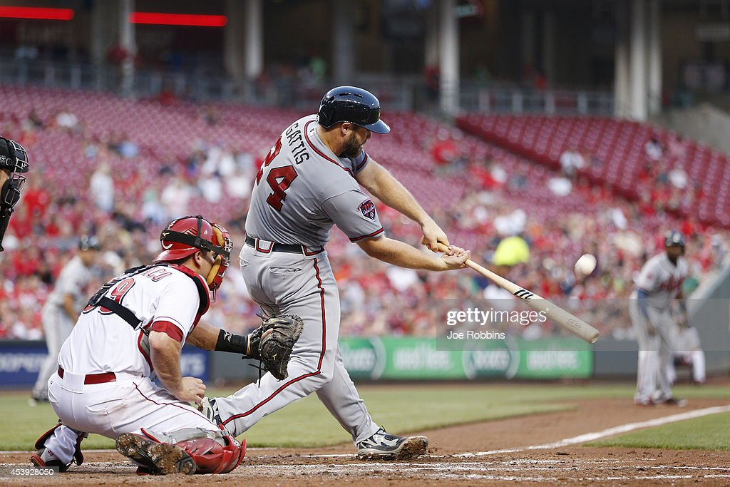 Evan Gattis #24 of the Atlanta Braves drives in a run with a sacrifice fly in the third inning of the game against the Cincinnati Reds at Great American Ball Park on August 21, 2014 in Cincinnati, Ohio.