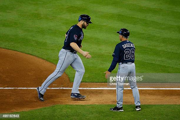 Evan Gattis of the Atlanta Braves is contratulated by third base coach Doug Dascenzo for a two run homerun in the ninth inning against the Miami...