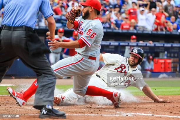 Evan Gattis of the Atlanta Braves scores on a past ball before Cesar Jimenez of the Philadelphia Phillies can make the tag in the sixth inning at...
