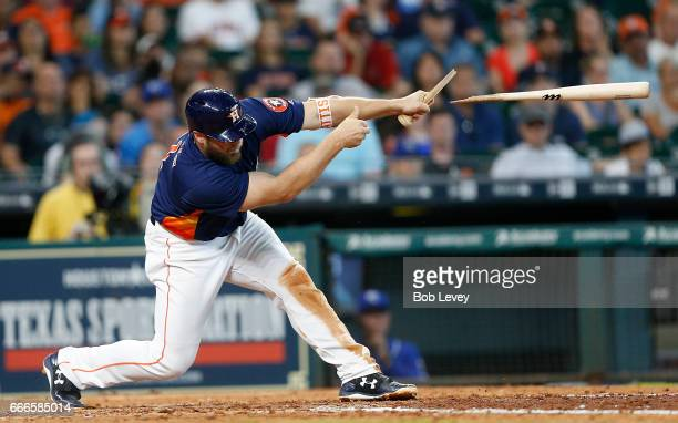 Evan Gattis of the Houston Astros breaks his bat as he singles in the eighth inning against the Kansas City Royals at Minute Maid Park on April 9,...