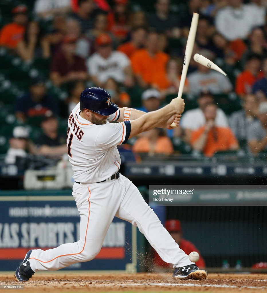 Evan Gattis #11 of the Houston Astros breaks his bat on foul ball off his foot in the eighth inning against the Los Angeles Angels of Anaheim at Minute Maid Park on April 19, 2017 in Houston, Texas.