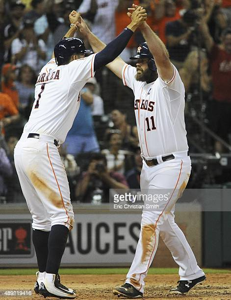Evan Gattis of the Houston Astros celebrates his threerun home run with Carlos Correa during the seventh inning against the Oakland Athletics at...