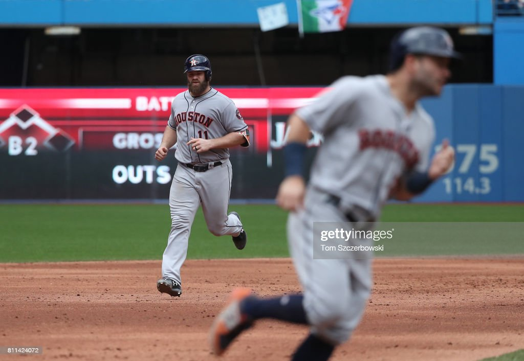 Evan Gattis #11 of the Houston Astros circles the bases with Jose Altuve #27 ahead of him after hitting a thre-run home run in the sixth inning during MLB game action against the Toronto Blue Jays at Rogers Centre on July 9, 2017 in Toronto, Canada.