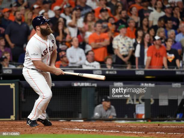 Evan Gattis of the Houston Astros hits a sac fly to score Alex Bregman in the bottom of the eighth inning Game 6 of the American League Championship...