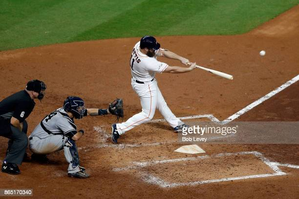 Evan Gattis of the Houston Astros hits a solo home run in the fourth inning against the New York Yankees in Game Seven of the American League...
