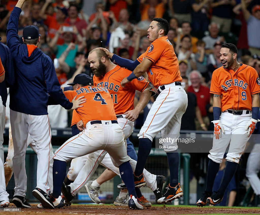 Evan Gattis #11 of the Houston Astros is congratulated by Marwin Gonzalez #9, Springer and Carlos Correa #1 after hitting a walk-off home run in the ninth inning against the Tampa Bay Rays at Minute Maid Park on August 26, 2016 in Houston, Texas.