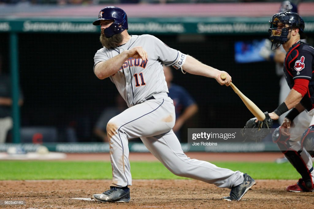 Evan Gattis #11 of the Houston Astros singles to left field to drive in two runs in the eighth inning against the Cleveland Indians at Progressive Field on May 25, 2018 in Cleveland, Ohio.