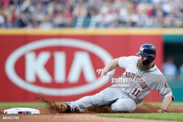 Evan Gattis of the Houston Astros slides at second base with a double in the third inning against the Cleveland Indians at Progressive Field on May...