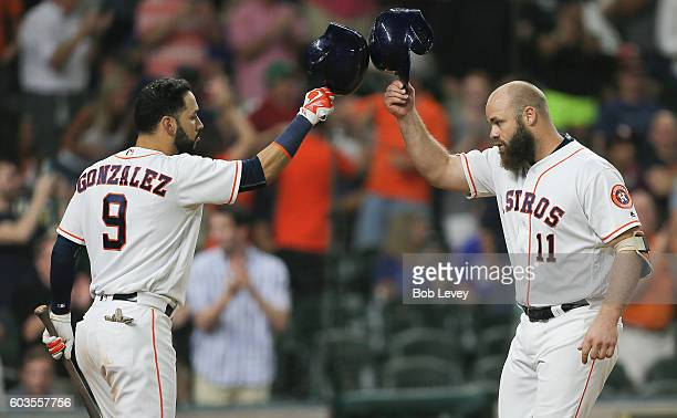 Evan Gattis of the Houston Astros taps helmets with Marwin Gonzalez after hitting a home run in the ninth inning against the Texas Rangers at Minute...