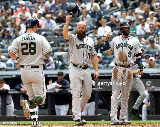 Evan Gattis of the Houston Astros tips his helmet to teammte J.D. Davis as he heads for home in the second inning at Yankee Stadium on May 28, 2018...