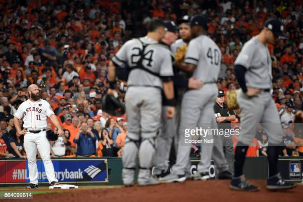 Evan Gattis of the Houston Astros waits at third durng a coaching visit to the mound in the bottom of the fifth inning of Game 6 of the American...
