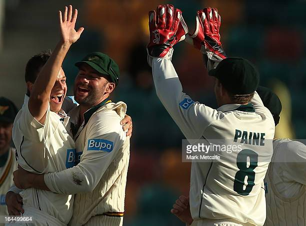 Evan Gulbis of the Tigers celebrates with Alex Doolan and Tim Paine after taking the wicket of Peter Forrest of the Bulls during day three of the...