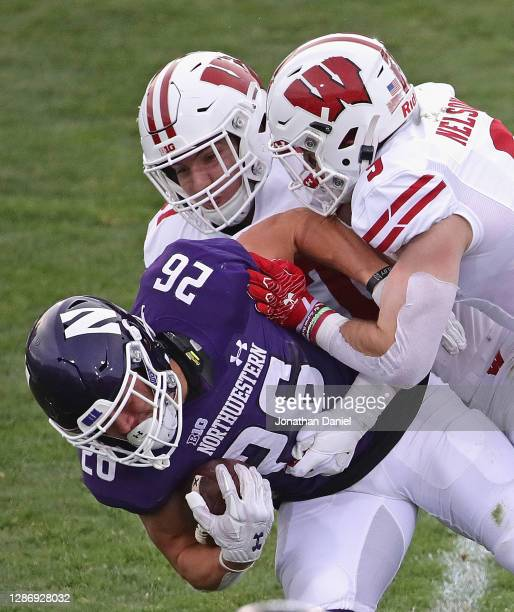 Evan Hull of the Northwestern Wildcats is dropped by Jack Sanborn and Scott Nelson of the Wisconsin Badgers at Ryan Field on November 21, 2020 in...