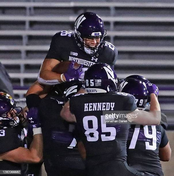 Evan Hull of the Northwestern Wildcats is lifted by teammates after running for a touchdown against the Maryland Terrapins at Ryan Field on October...