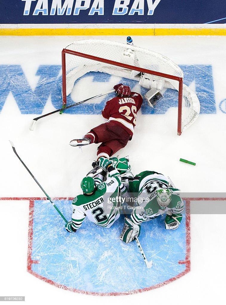 Evan Janssen #26 of the Denver Pioneers crashes into Cam Johnson and Troy Stecher #2 both of the North Dakota Fighting Hawks during game two of the 2016 NCAA Division I Men's Hockey Frozen Four Championship Semifinal at the Amaile Arena on April 7, 2016 in Tampa, Florida. The Fighting Hawks won 4-2.