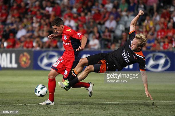 Evan Kostopoulos of Adelaide is tackled by Mitchell Nichols of Brisbane during the round 13 ALeague match between Adelaide United and the Brisbane...