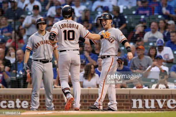 Evan Longoria and Scooter Gennett of the San Francisco Giants celebrate after Longoria hit a home run in the first inning against the Chicago Cubs at...