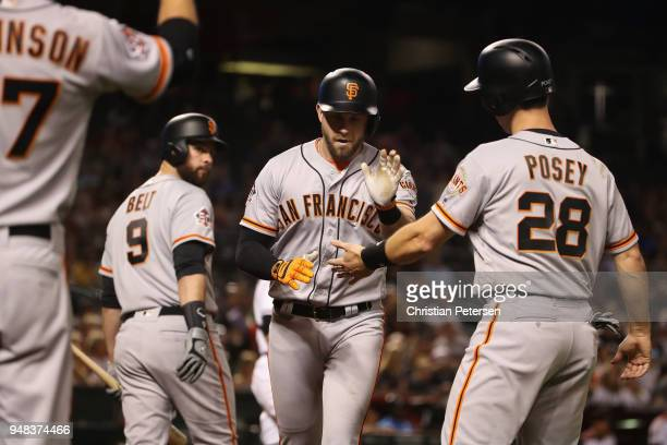 Evan Longoria of the San Francisco Giants high fives Brandon Belt and Buster Posey after hitting a tworun home run against the Arizona Diamondbacks...