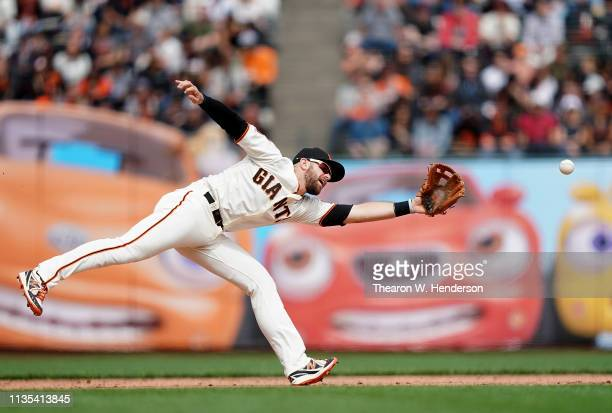 Evan Longoria of the San Francisco Giants reacts and watches the ball go into left field for a base hit off the bat of pitch-hitter Willy Adames of...