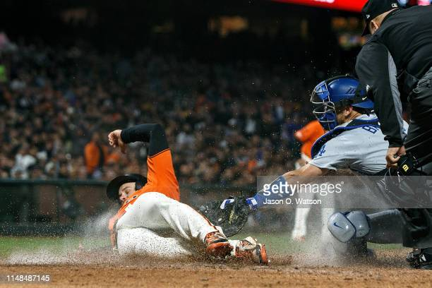 Evan Longoria of the San Francisco Giants slides under a tag from Austin Barnes of the Los Angeles Dodgers to score a run during the sixth inning at...