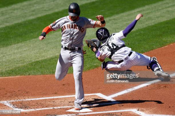 Evan Longoria of the San Francisco Giants touches home plate to score ahead of the tag by Tony Wolters of the Colorado Rockies during the first...