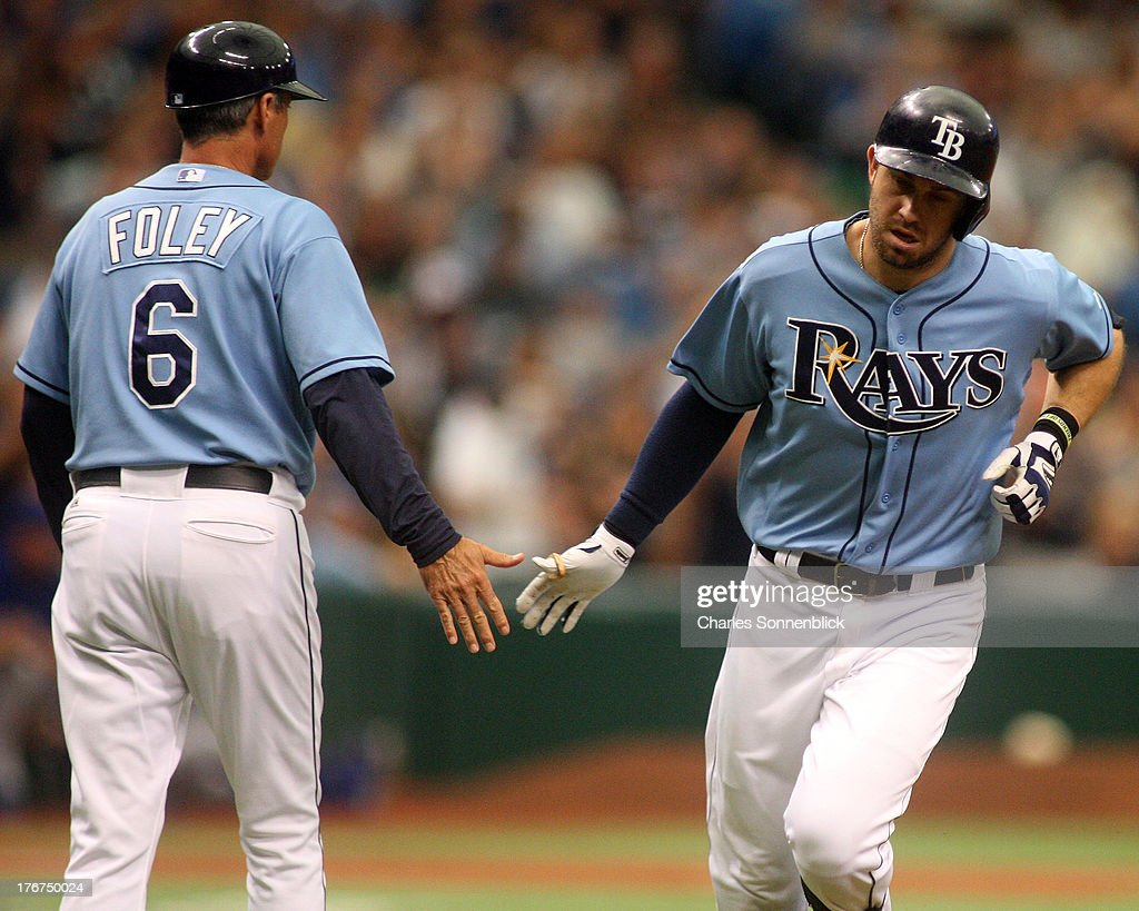 Evan Longoria #3 of the Tampa Bay Rays hits a homerun and slaps five with third base coach Tom Foley #6 in the first inning against the Toronto Blue Jays during the game on August 18, 2013 at Tropicana Field in St. Petersburg, Florida.