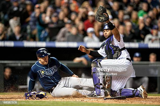 Evan Longoria of the Tampa Bay Rays is tagged out at home plate by Wilin Rosario of the Colorado Rockies in the eighth inning of a game at Coors...
