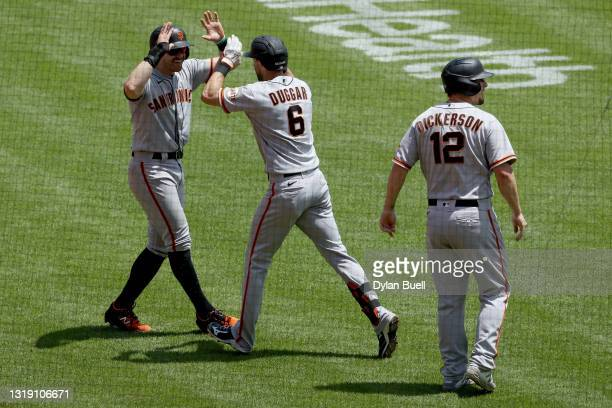Evan Longoria, Steven Duggar, and Alex Dickerson of the San Francisco Giants celebrate after Duggar hit a grand slam in the third inning against the...