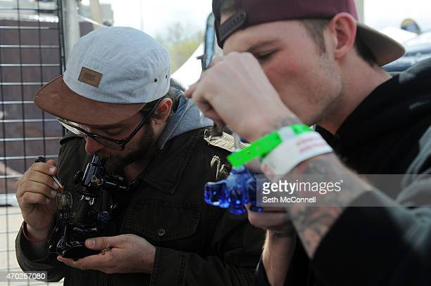 Evan Mann left does a dab out of a microscope shaped rig during the High Times Cannabis Cup at the Denver Mart in Denver Colorado on April 18 2015...