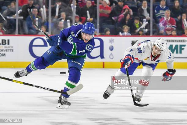 Evan McEneny of the Utica Comets dumps the puck while Kenny Agostino of the Laval Rocket tries to stop him at Place Bell on November 3 2018 in Laval...
