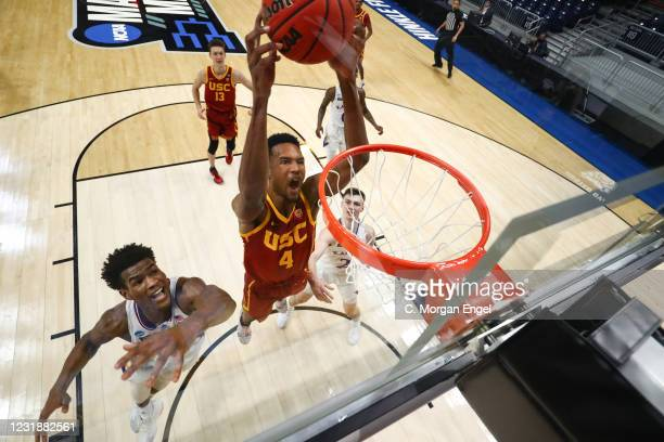 Evan Mobley of the USC Trojans dunks on Ochai Agbaji of the Kansas Jayhawks during the first half in the second round of the 2021 NCAA Division I...
